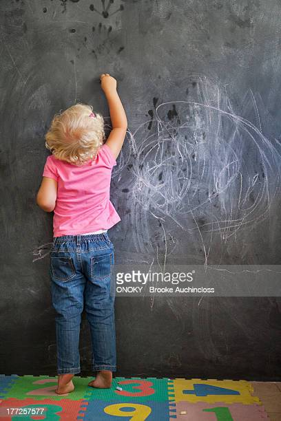 Rear view of a girl writing on a blackboard