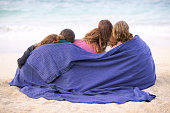 Rear view of a group of friends sitting on the beach wrapped together in a blanket