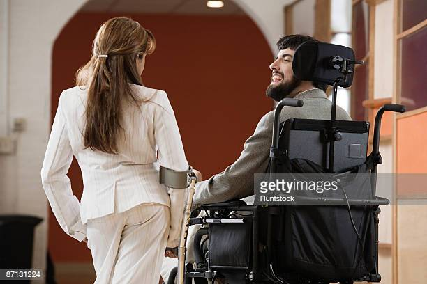 Rear view of a handicapped man and woman conversing.