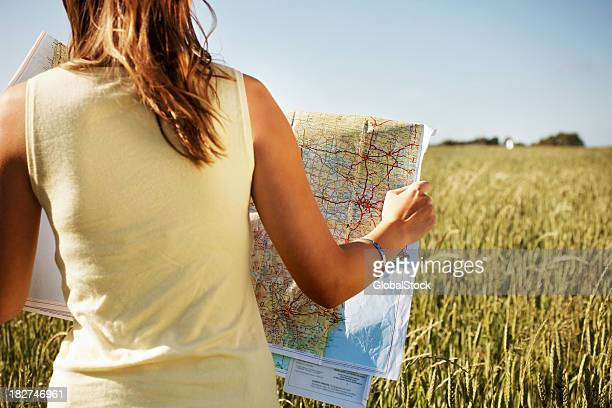 Rear view of a lady with road map in field