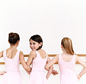 Rear View of a Line of Young, Female Ballet Dancer Practicing in the Dance Studio With One Ballerina Looking Behind Her