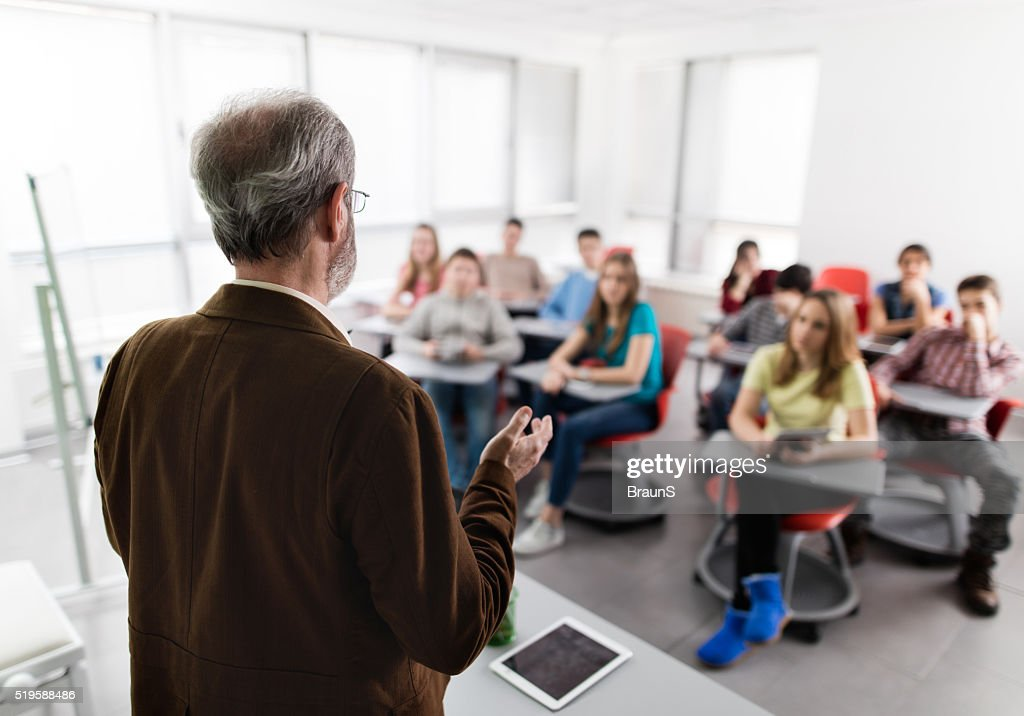 Rear view of a male teacher giving a lecture. : Stock Photo
