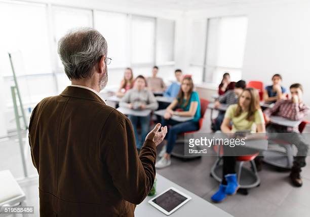 Rear view of a male teacher giving a lecture.