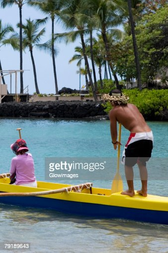 Rear view of a man and a woman canoeing in the sea, Captain Cook's Monument, Kealakekua Bay, Kona Coast, Big Island, Hawaii islands, USA : Foto de stock