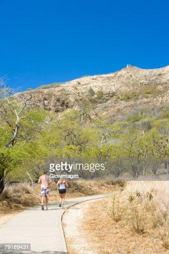 Rear view of a man and a woman running on a path, Diamond Head, Waikiki Beach, Honolulu, Oahu, Hawaii Islands, USA : Stock Photo