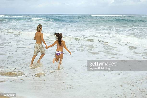 Rear view of a man and a woman running on the beach