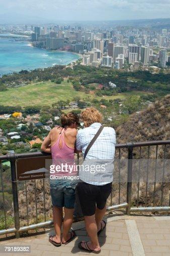 Rear view of a man and a woman standing at an observation point, Diamond Head, Waikiki Beach, Honolulu, Oahu, Hawaii Islands, USA : Stock Photo