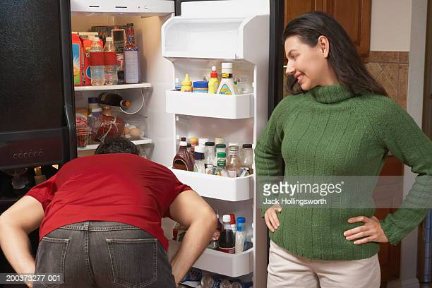 Rear view of a man bending forward looking into a refrigerator with a young woman standing beside him