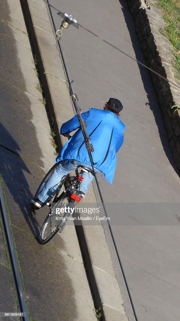 Rear View Of A Man Bicycling On Road : Stock-Foto