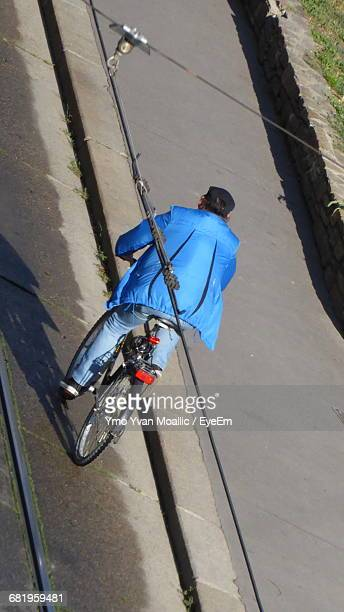 Rear View Of A Man Bicycling On Road