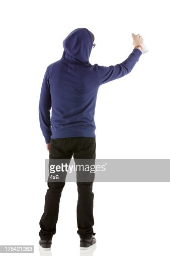 Rear view of a man doing graffiti