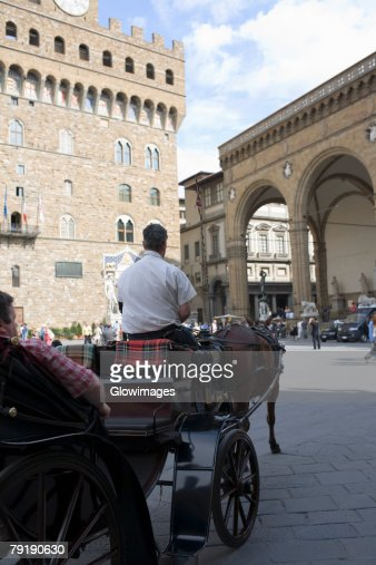 Rear view of a man driving a horsedrawn carriage, Portico of the Lansquenetes, Florence, Italy : Stock Photo