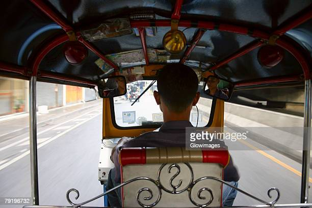 Rear view of a man driving a tuk-tuk, Bangkok, Thailand