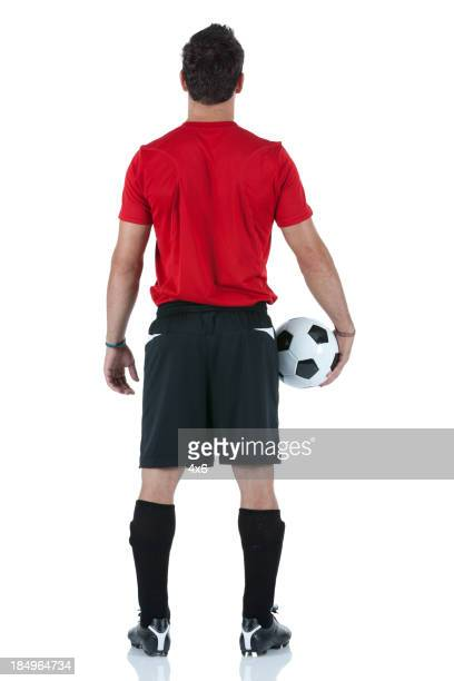 Rear view of a man holding soccer ball