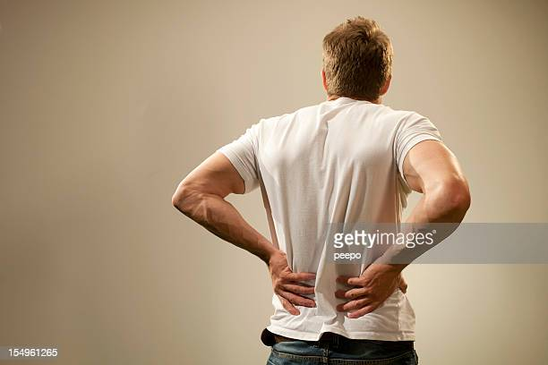 Rear view of a man in t-shirt holding his back in pain.