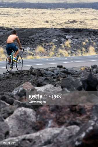 Rear view of a man riding a bicycle on the road, Kona Coast, Big Island, Hawaii Islands, USA : Foto de stock