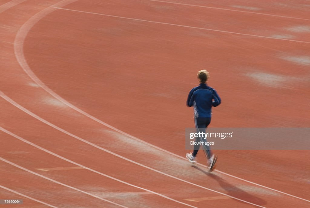 Rear view of a man running on a sports track : Foto de stock
