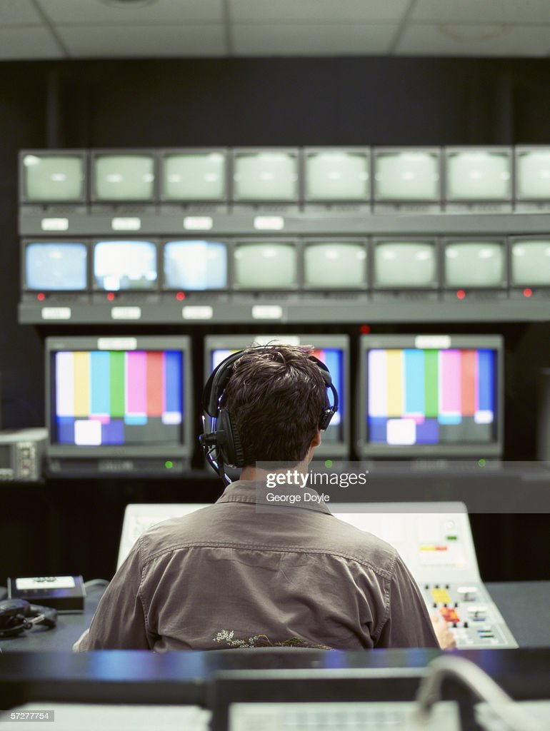 Rear view of a man sitting in a control room in a tv studio
