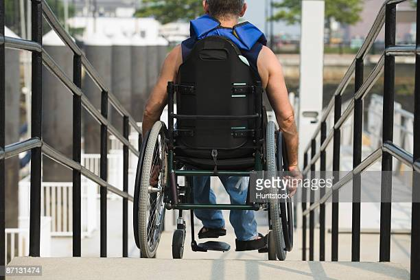 Rear view of a man sitting in a wheelchair on a wheelchair ramp