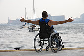 Rear view of a disabled man sitting in a wheelchair with his arm outstretched at a harbor