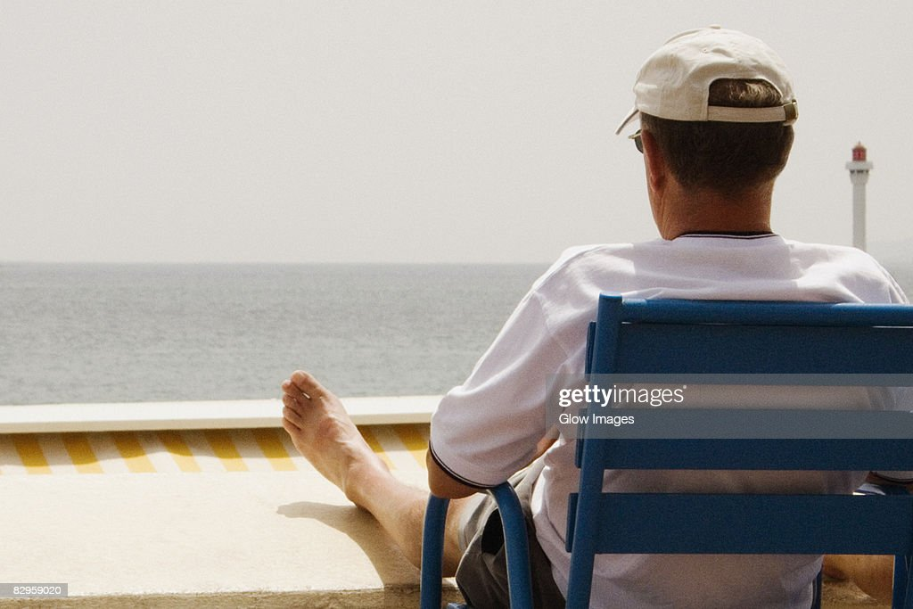 Rear view of a man sitting in an armchair on the beach, Baie De Cannes, Provence-Alpes-Cote D'Azur, France