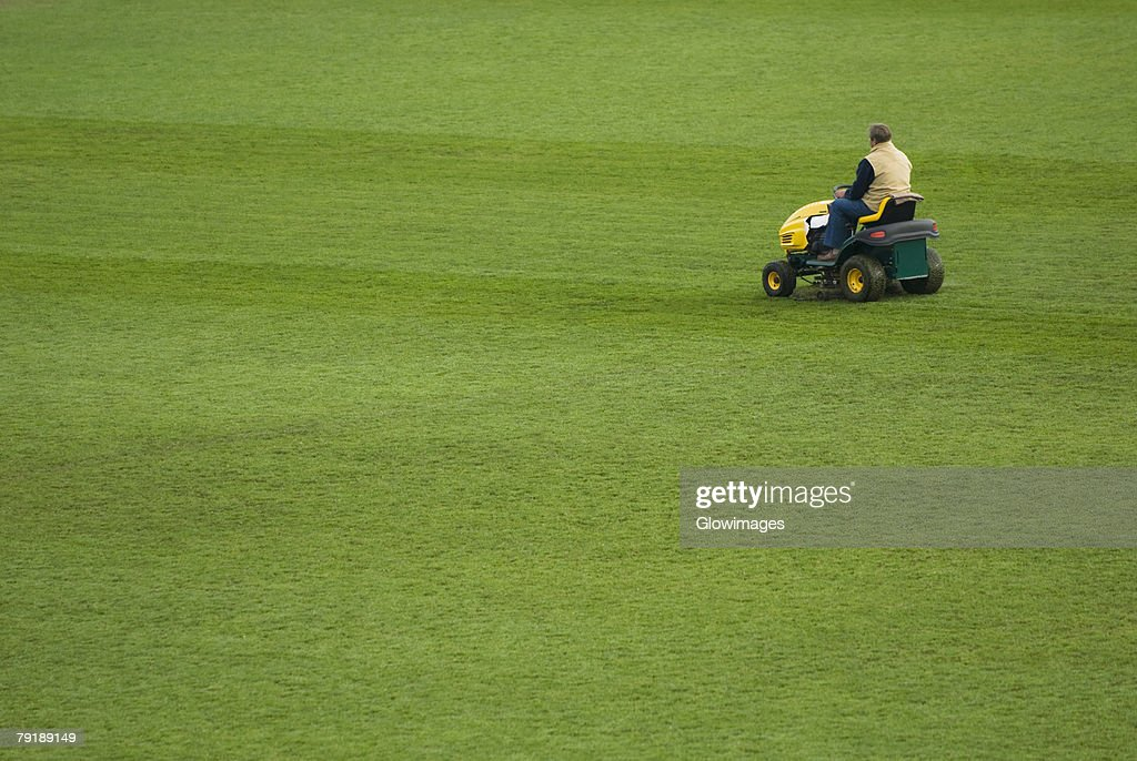 Rear view of a man sitting on a lawn mower : Stock Photo