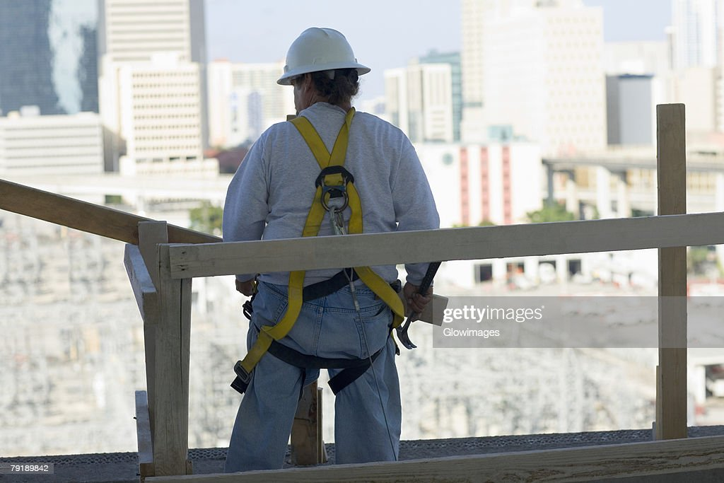 Rear view of a man standing and holding a hammer : Foto de stock