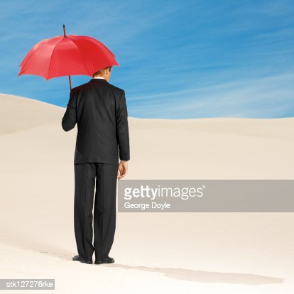 rear view of a man standing holding an umbrella : Stock Photo