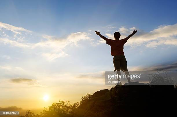 Rear view of a man standing on a rock at sunset feeling free