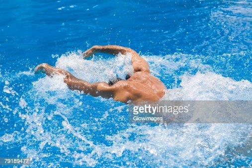 Rear view of a man swimming the butterfly stroke in a swimming pool : Foto de stock