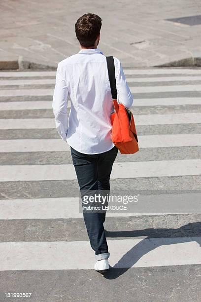Rear view of a man walking in crosswalk, Paris, Ile-de-France, France