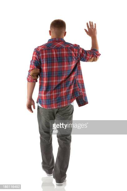 Rear view of a man waving hands