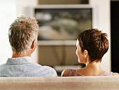 Rear View of a Mature Couple Sitting Side-By-Side on a Sofa Watching TV