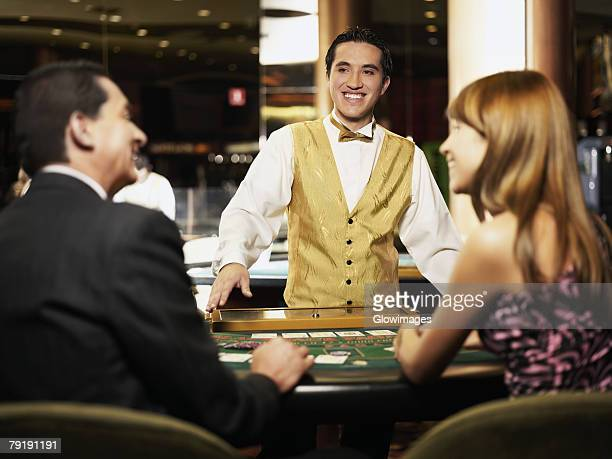 Rear view of a mature man and a young woman sitting at a gambling table with a casino worker smiling in front of them