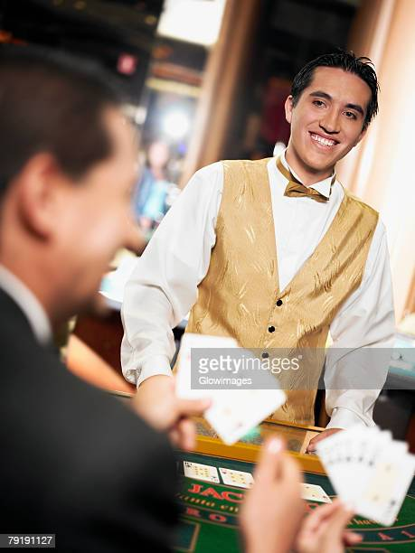 Rear view of a mature man holding playing cards with a casino worker standing in front of him