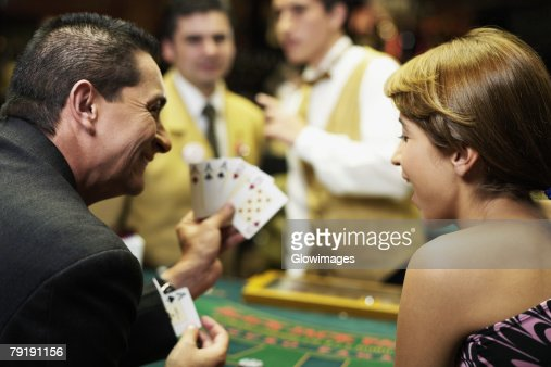Rear view of a mature man showing playing cards to a young woman in a casino : Foto de stock