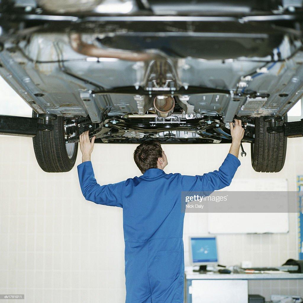 Rear View of a Mechanic Working Underneath a Car, Raised on a Hydraulic Platform