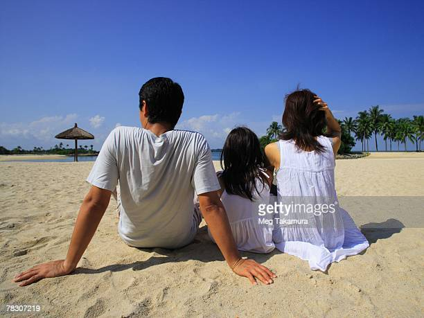 Rear view of a mid adult couple sitting on the beach with their daughter