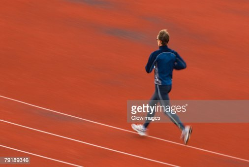 Rear view of a mid adult man running on a running track : Stock Photo
