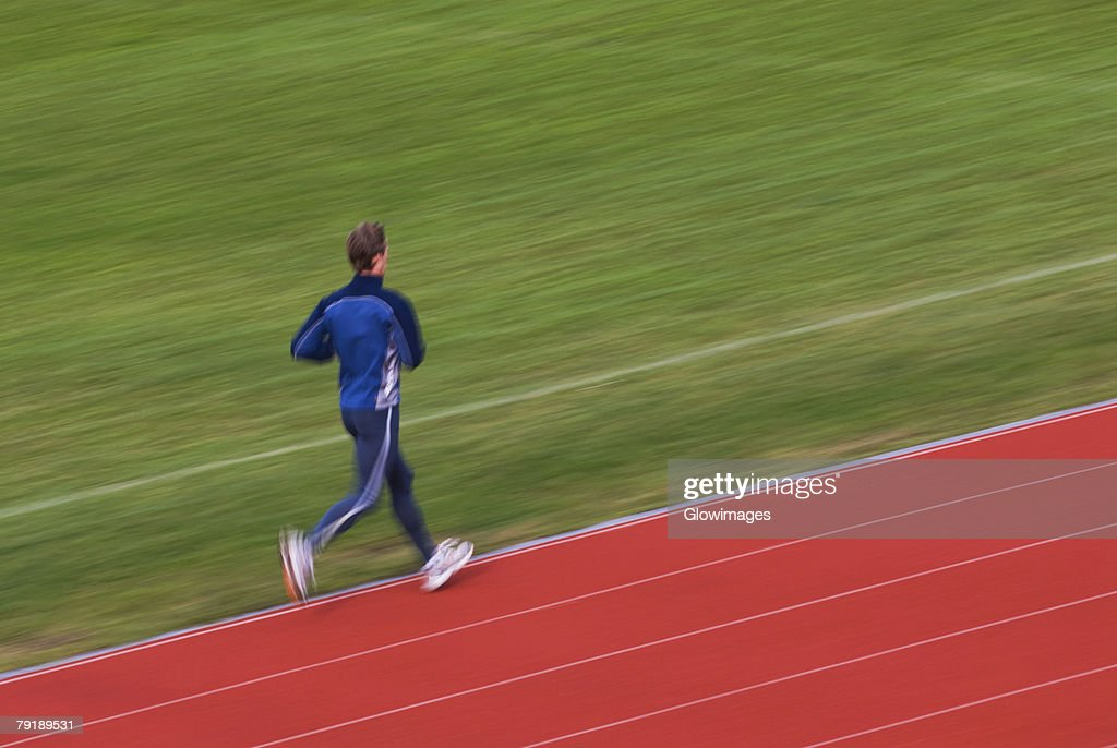 Rear view of a mid adult man running on a running track : Foto de stock