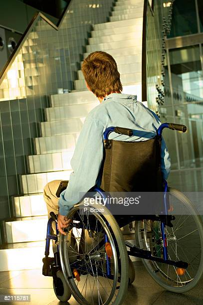 Rear view of a mid adult man sitting in a wheelchair and looking at a staircase