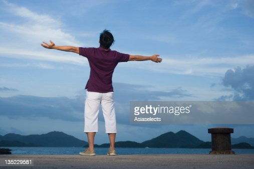Rear view of a mid adult man standing on the beach with his arm outstretched