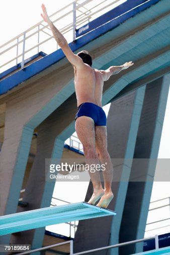 Rear view of a mid adult man taking start from a diving platform : Foto de stock