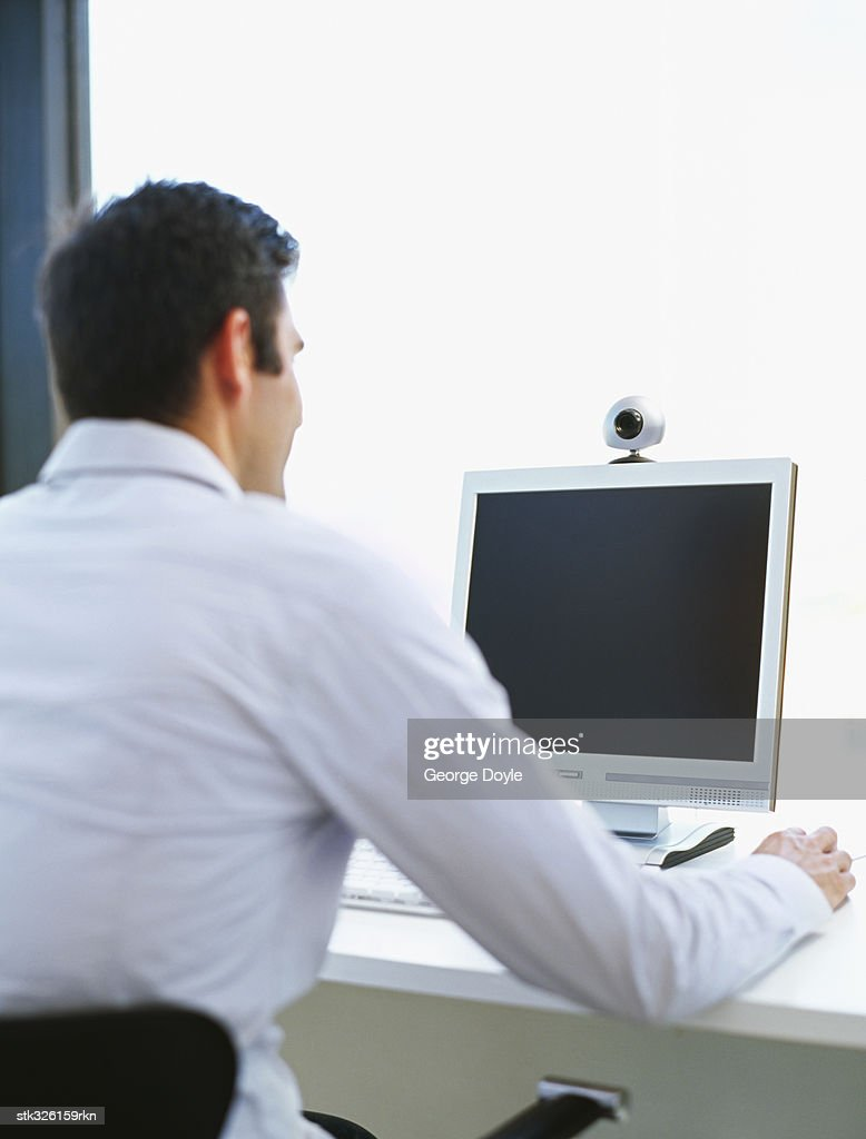rear view of a mid adult man using a computer : Stock Photo