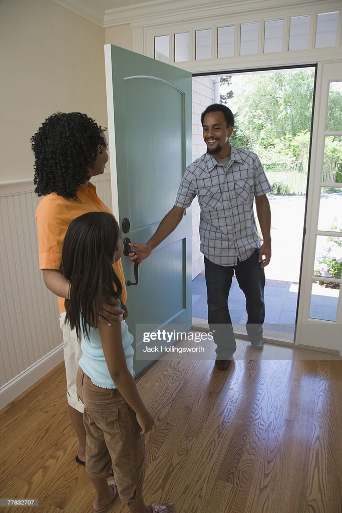 Rear view of a mid adult woman and her daughter greeting a young man at the front door : Stock Photo