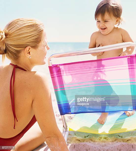 Rear view of a mother on the beach playing with her baby boy