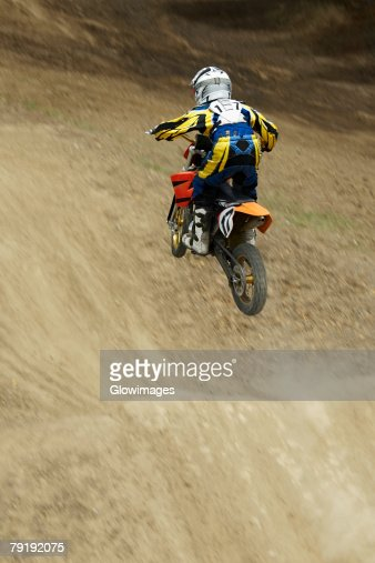 Rear view of a motocross rider performing jump on a motorcycle : Stock Photo
