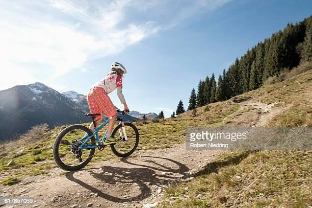 'Rear view of a mountain biker riding on uphill, Saalbach-Hinterglemm, Zell am See, Salzburg, Austria'