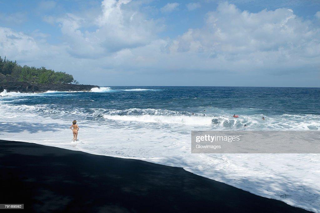 Rear view of a naked woman standing on the beach, Kehena Beach, Big Island, Hawaii Islands, USA : Foto de stock