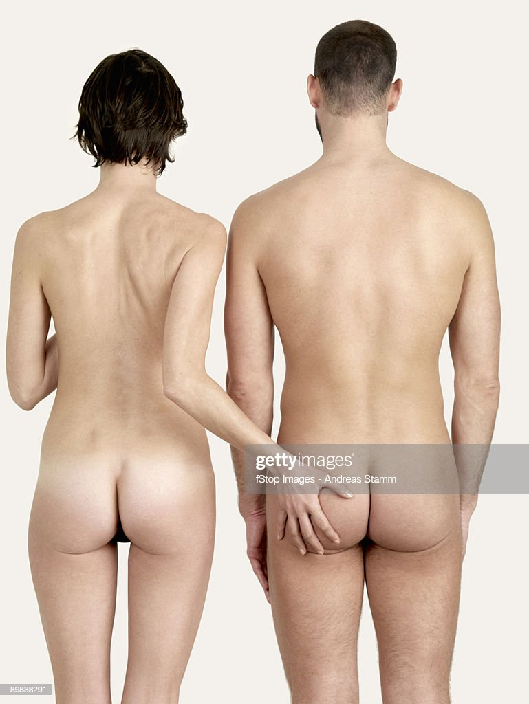 Rear view of a naked woman touching a naked man's bottom : Stock Photo